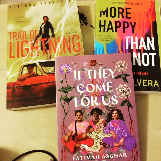 three books. if they should come for us by fatimah asghar on top of, trail of lightning by rebecca roanhoarse on the left and more happy than not by adam silvera on the right.