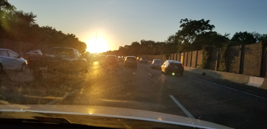 a picture taken in the passenger seat of the car as the driver rides alone the highway. there are cars on all sides, with trees surrounding the road and a big sunset in front of the cars.